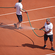 PARIS, FRANCE June 12.  Ground staff water the clay court between sets during the Barbora Krejcikova of the Czech Republic match against Anastasia Pavlyuchenkova of Russia on Court Philippe-Chatrier during the final of the singles competition at the 2021 French Open Tennis Tournament at Roland Garros on June 12th 2021 in Paris, France. (Photo by Tim Clayton/Corbis via Getty Images)
