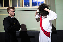 © Licensed to London News Pictures . 27/12/2016 . Wigan , UK . A man dressed as Jesus Christ puts on a large curly black wig as another man dressed as a clergyman walks by . Revellers in Wigan enjoy Boxing Day drinks and clubbing in Wigan Wallgate . In recent years a tradition has been established in which people go out wearing fancy-dress costumes on Boxing Day night . Photo credit : Joel Goodman/LNP