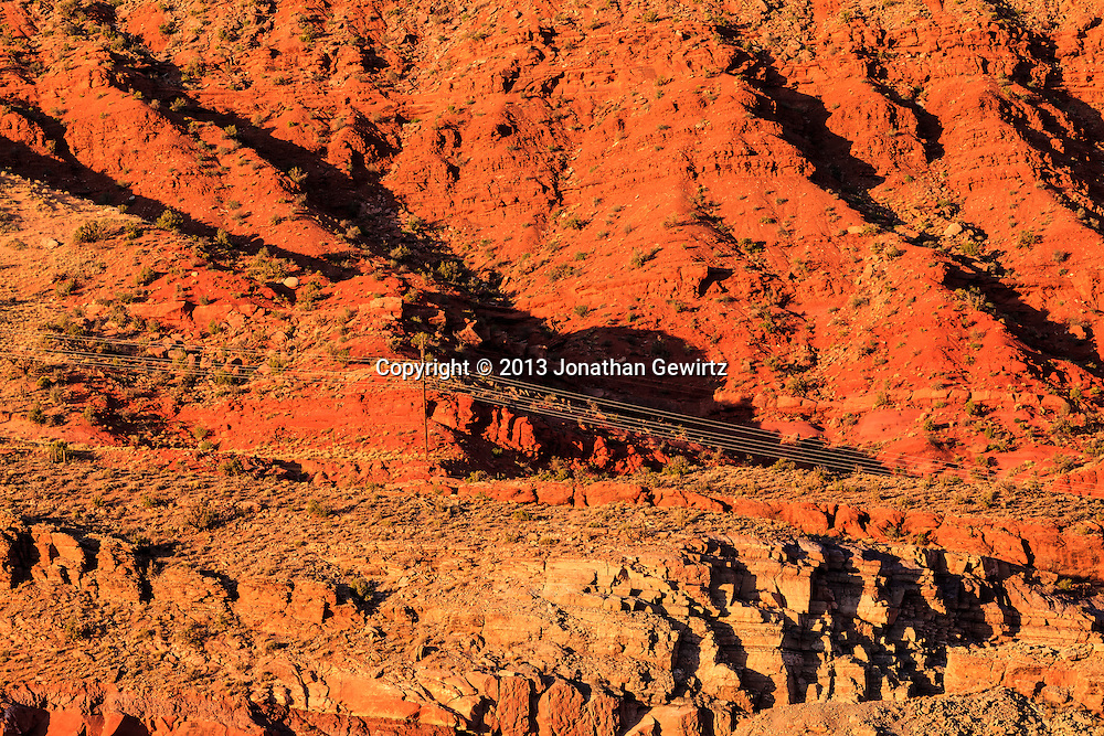 The morning sun lights up colorful rock strata in the Moab Fault, next to US Route 191 and Arches National Park, Utah. WATERMARKS WILL NOT APPEAR ON PRINTS OR LICENSED IMAGES.