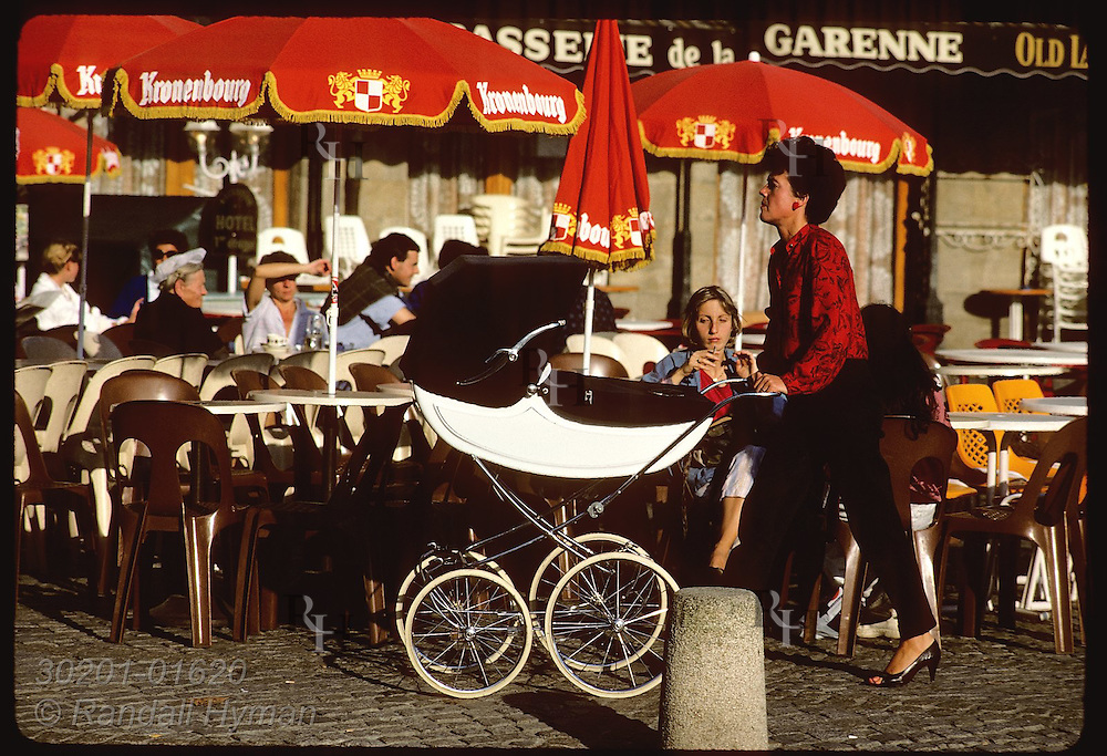 People sitting at tables of outdoor cafe in Vannes, Brittany as woman walks buy pushing pram. France