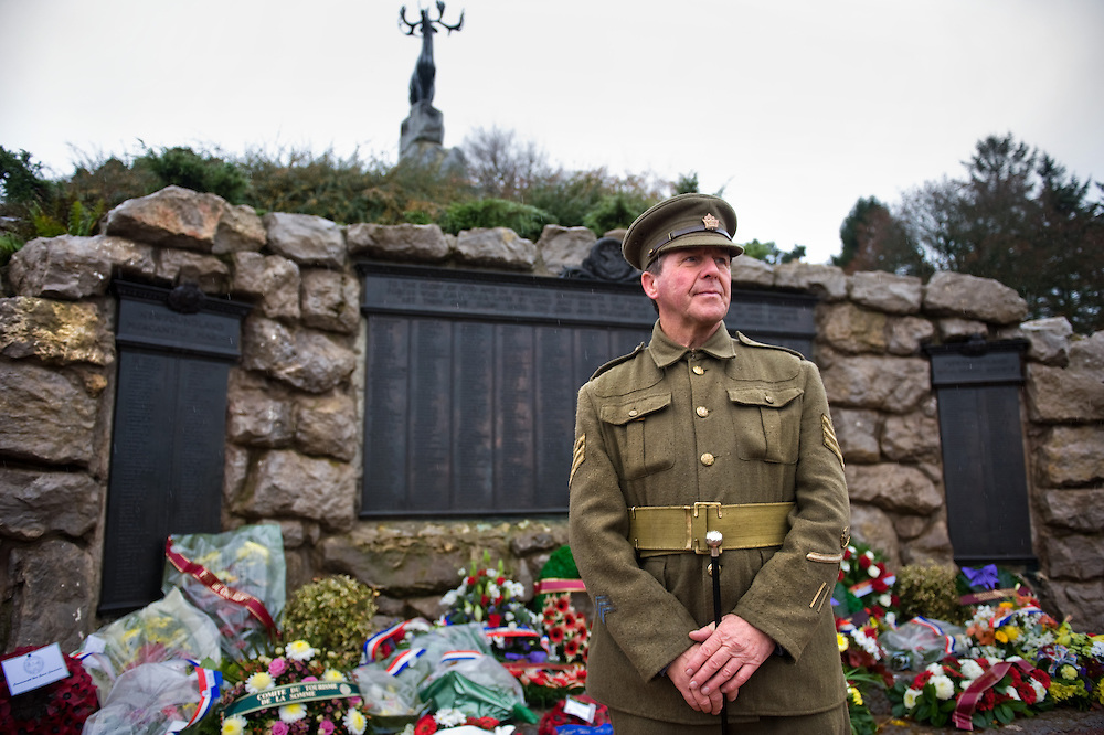 A man dressed with a Canadian Expeditionary Force  officers uniform standing in front of the Beaumont-Hamel Newfoundland Memorial. On the back are the three bronze tablets that carry the names of 820 members of the Royal Newfoundland Regiment, the Newfoundland Royal Naval Reserve, and the Mercantile Marines who died in the First World War and have no known grave. The Caribou Memorial, the emblem of the Royal Newfoundland Regiment, standing atop a mound of Newfoundland granite. Beaumont-Hamel Newfoundland Memorial is dedicated to the commemoration of the Newfoundland Regiment that fought in the battle of Somme and WWI in general. Most of the  Newfoundland Regiment were dead within 15 to 20 minutes of leaving their trench in the morning of the 1st July 1916 during the first day of the Battle of the Somme.