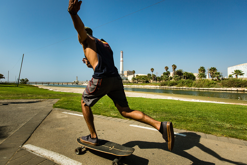 Backdropped by The Reading Power Station, a man is seen skating along the river bank of The Yarkon River in Tel Aviv's Tzafon Yashan neighborhood