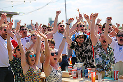 © Licensed to London News Pictures. 13/06/2021. London, UK. Fans react at Skylight Rooftop, Tobacco Dock in London, after England's Raheem Sterling scores a goal, in their opening Euro 2020 game against Croatia. Photo credit: Dinendra Haria/LNP