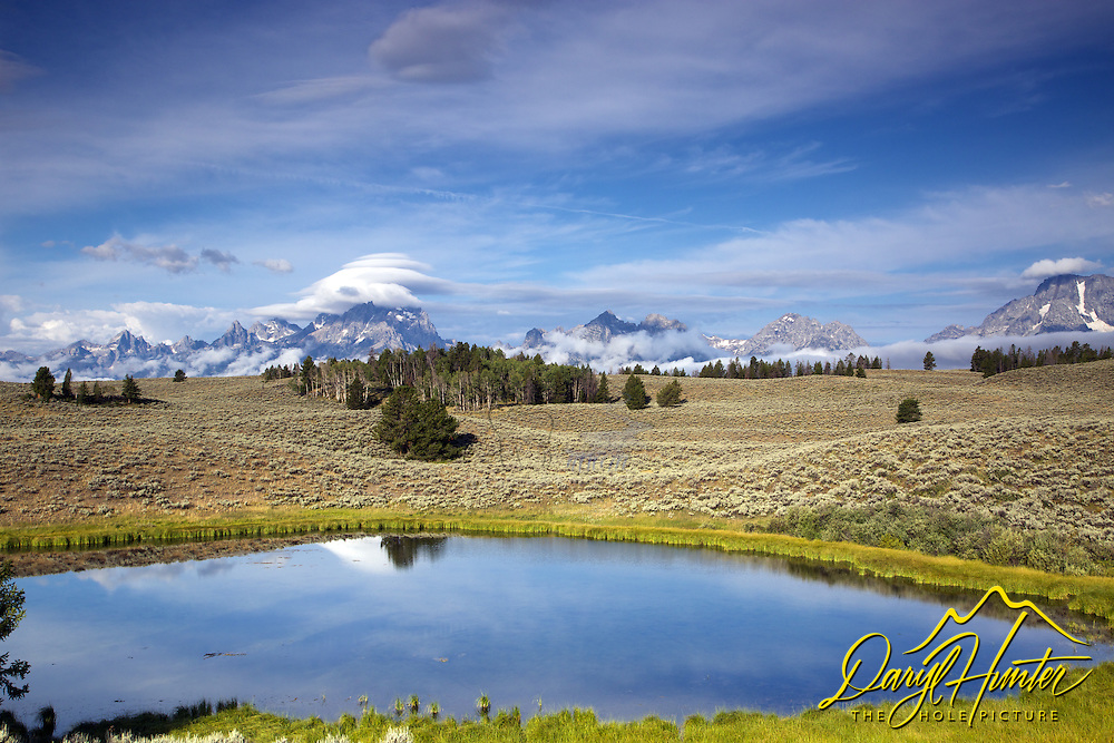 Lenticular  clouds over the Grand Tetons at Daryl's Pond in Grand Teton National Park<br />