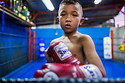 """18 DECEMBER 2104 - BANGKOK, THAILAND: Portrait of a young boxer at the Kanisorn gym. The Kanisorn boxing gym is a small gym along the Wong Wian Yai - Samut Sakhon train tracks. Young people from the nearby communities come to the gym to learn Thai boxing. Muay Thai (Muai Thai) is a Thai fighting sport that uses stand-up striking along with various clinching techniques. It is sometimes known as """"the art of eight limbs"""" because it is characterized by the combined use of fists, elbows, knees, shins, being associated with a good physical preparation that makes a full-contact fighter very efficient. Muay Thai became widespread internationally in the twentieth century, when practitioners defeated notable practitioners of other martial arts. A professional league is governed by the World Muay Thai Council. Muay Thai is frequently seen as a way out of poverty for young Thais and Muay Thai camps and schools are frequently crowded. Muay Thai professionals and champions are often celebrities in Thailand.     PHOTO BY JACK KURTZ"""