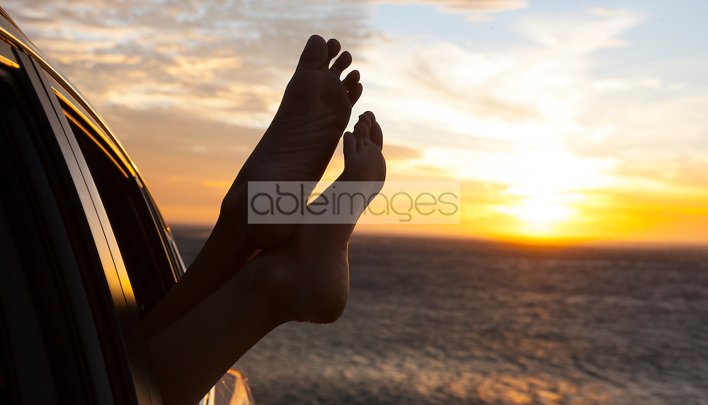 Woman's Feet Sticking out of Car Window at Sunset by Ocean