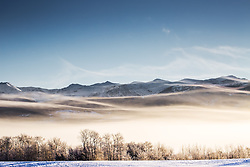 Frosty and foggy morning in Teton Valley Idaho.  A ground fog covers the valley and as the sun clears the mountains a new layer of fog appears over the ridges of the lower peaks of the Grand Tetons.