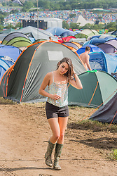 It is a long walk back from hair washing in the sinks at the toilets. The 2015 Glastonbury Festival, Worthy Farm, Glastonbury.