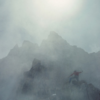 A mountaineer approaches the foggy summit of Mount Humphreys on the crest of California's Sierra Nevada.