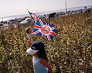 Young aviation fan of the Red Arrows, Britain's RAF aerobatic team, holds up an RAF merchandise brolley during airshow.
