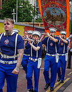 Each year, members of the Orange Order - named after the victorious king and founded in 1795 - carry banners and flags in parades across Northern Ireland accompanied by marching bands playing pipes and drums.<br /> Orange March, Belfast, NI,2021