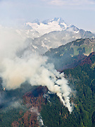 """Forest fire on Downey Creek, seen from Green Mountain hike. Dome Peak rises above. Trail head is on the Mountain Loop Highway, Washington, USA. Published in """"Light Travel: Photography on the Go"""" by Tom Dempsey 2009, 2010."""