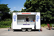 A young female cook reads a newspaper at a roadside burger van on 16th June 2008 in West Basingstoke in the United Kingdom.