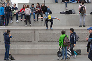 Watched by his friends, a young visitor to the capital prepares to jump off one of the plinths beneath Nelson's Column in Trafalgar Square, on 20th May 2019, in London, England.