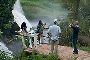 Central African Republic. August 2012. Boali waterfalls. Two white men with two young local women, taking a photo.