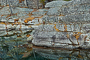 Rocky shoreline reflected in Horseshoe Lake<br /> Jasper National Park<br /> Alberta<br /> Canada