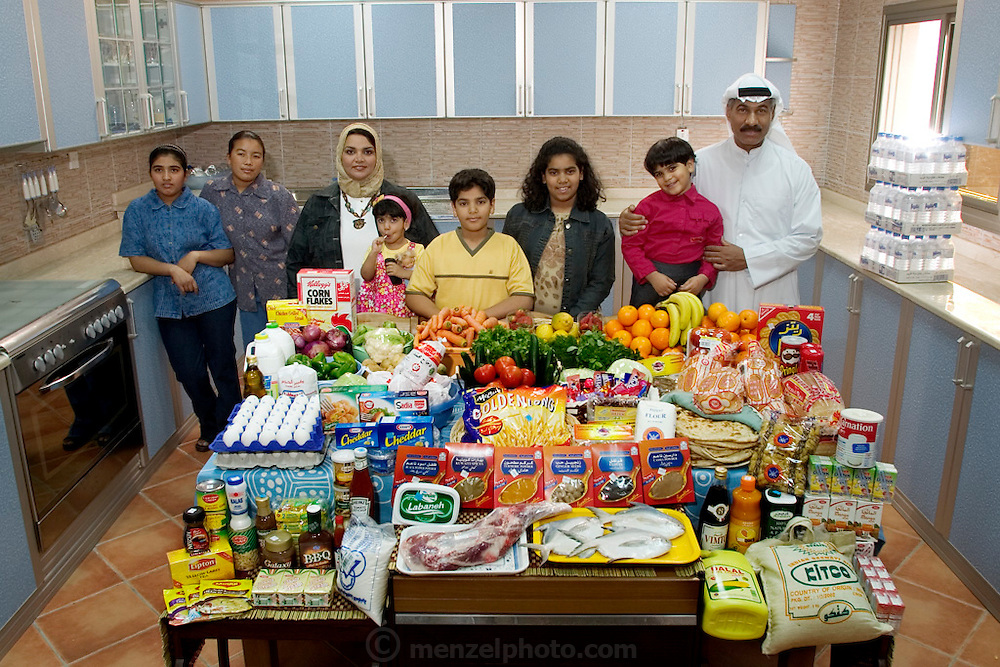 (MODEL RELEASED IMAGE). The Al Haggan family and their two Nepali servants in the kitchen of their home in Kuwait City, Kuwait, with one week's worth of food. Standing between Wafaa Abdul Aziz Al Qadini, 37 (beige scarf), and Saleh Hamad Al Haggan, 42, are their children, Rayyan, 2, Hamad, 10, Fatema, 13, and Dana, 4. In the corner are the servants, Andera Bhattrai, 23 (left), and Daki Serba, 27. The Al Haggan family is one of the thirty families featured in the book Hungry Planet: What the World Eats (p. 196).