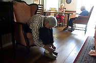 An Alzheimer's patient ties her shoe at a live-in residence for Alzheimer's and dementia related  patients.