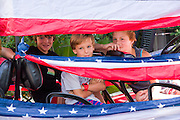 Young children peak out from behind patriotic bunting in their golf cart during the I'On neighborhood Independence Day parade July 4, 2015 in Mt Pleasant, South Carolina.