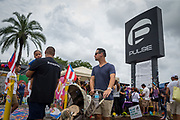 On the one-year anniversary of the Pulse shooting, Angel Santiago walks past the nightclub memorial with brother Sam Santiago and baby nephew Roman in Orlando, Florida, U.S.