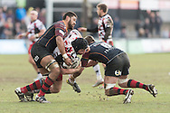 Alasdair Dickinson of Edinburgh rugby (c)  is tackled by Lewis Evans (r) and Taulupe Faletau (l) of the Newport Gwent Dragons. Guinness Pro12 rugby match, Newport Gwent Dragons v Edinburgh Rugby at Rodney Parade in Newport, South Wales on Sunday 27th March 2016.<br /> pic by  Simon Latham, Andrew Orchard sports photography.
