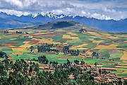 Agricultural fields form a checkerboard outside an Andes highland village near the Cordillera Vilcabamba mountains, Peru, South America.