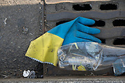 """April, 16th 2020 - Paris, Ile-de-France, France: Masks and gloves thrown away on the sidewalk during the Coronavirus pandemic. Used protection from the spread of the Coronavirus, during the third week of near total lockdown imposed in France. A week after President of France, Emmanuel Macron, said the citizens must stay at home for at least 15 days, that has been extended. He said """"We are at war, a public health war, certainly but we are at war, against an invisible and elusive enemy"""". All journeys outside the home unless justified for essential professional or health reasons are outlawed. Anyone flouting the new regulations is fined. Nigel Dickinson"""