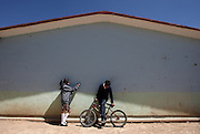 ORG XMIT: *S0423398412* (03/05/08) -- A pair casually chats while leaning on the side of one of the buildings comprising the telesecundaria in the ranching community of El Mezquite. Telesecundarias are junior high schools that have television sets in every classroom, broadcasting the same lesson at the same time nationwide. Teachers are present so that in between broadcasts students complete workbook assignments and participate in group discussions.<br /> 06092008xNEWS