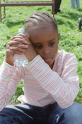 Young girl looking thoughtful whilst sitting in the park