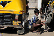 A man works on repairing the rear tires of a rickshaw.  The slum of Cheetah Camp on the outskirts of Mumbai, India is a predominantly muslim community on living on the fringe while the city continues to grow.