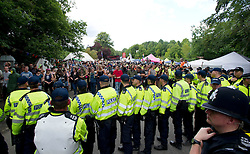 © London News Pictures. 19/08/2013. Balcombe, UK.  Police line up as they prepare to remove activists from in front of the entrance to the Cuadrilla drilling site in Balcombe, West Sussex on a day of of civil disobedience organised by campaign group No Dash For Gas. Cuadrilla has temporarily ceased drilling at the site, which has been earmarked for fracking, under advice from the police. Photo credit: Ben Cawthra/LNP