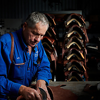 Lyle Kent working leather to make a  saddle at his Stanthorpe factory, QLD