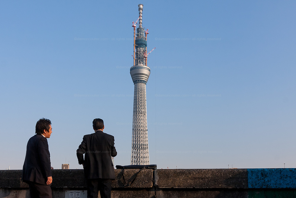 Two Japanese salarymen take in the the view of Tokyo Skytree under construction. Oshiage, Tokyo, Japan. Friday February 4th 2011. When finished this telecommunications tower will measure 634 metres from top to bottom making it the tallest structure in East Asia..