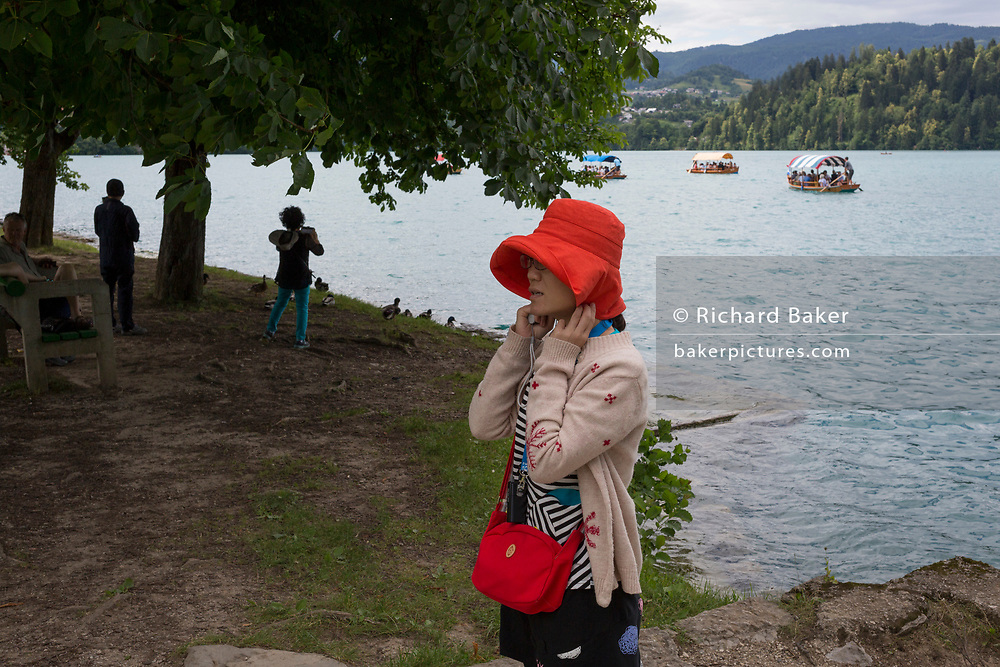 Chinese coach tourists enjoy the views vrom the shore of Lake Bled, on 18th June 2018, in Bled, Slovenia.