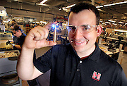 Everett Deger, Marketing Communications Manager at Hornady Manufacturing holds up a 25-06 cartridge being inspected in the Ammunition Inspection Division of Hornady Manufacturing Co. in Grand Island on Wednesday. (Independent/Crystal LoGiudice)..