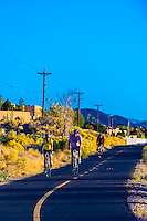 Bicyclists riding on a path alongside Tramway Boulevard, Albuquerque, New Mexico USA.