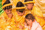 Young girls in traditional dress hiding at Novitation Ceremony, Mandalay