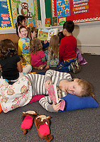 Piper Dion gets comfortable with her book while the rest of her group listens to a story told by parent volunteer Tamara Van Lenten Tuesday evening at Holy Trinity Catholic School.  (Karen Bobotas/for the Laconia Daily Sun)