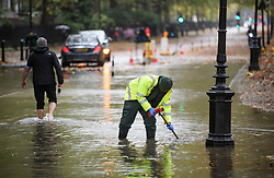 © Licensed to London News Pictures. 24/10/2019. London, UK. Workers attempt to unblock the drains on the roads near St James's Park in Westminster which flooded during a heavy downpour of rain. Photo credit: Ben Cawthra/LNP
