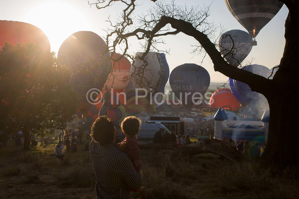 A father watches with his child, the mass lift-off by balloons at Bristols annual fiesta at Ashton Court, UK. Taking off into early morning summer skies above England's southwest City, the airships rise from the heat of hot air burners. Crowds from across the city arive with picnics and children to sit and wait for the green smoke that signals a Go. Once airbourne, the balloons start to climb only a short distance, to land a few hundred metres away on this particular morning's stll air conditions. The 37th Bristol International Balloon Fiesta is billed as Europe's largest (and free) ballooning event. Bristol's local ballooning entrepreneur hero is Don Cameron whose balloons are known worldwide.