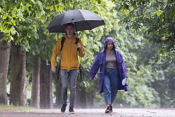 © Licensed to London News Pictures. 27/07/2021. London, UK. A man uses an umbrella to shelter from rain in Greenwich Park in South East London. A yellow weather warning for thunderstorms is in place for parts of England. Photo credit: George Cracknell Wright/LNP