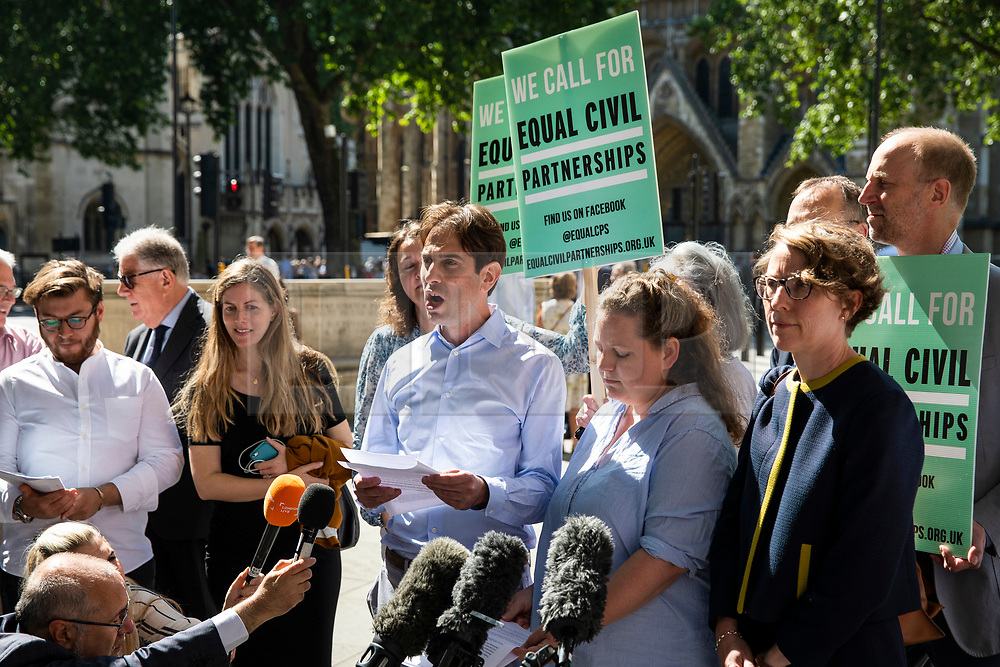 """© Licensed to London News Pictures. 27/06/2018. London, UK. Rebecca Steinfeld (centre-right) and Charles Keidan (centre), who have """"deep-rooted"""" ideological objections to the institution of marriage, speak to the press after Supreme Court judges ruled in their favour in their legal battle to grant heterosexual couples the right to enter into civil partnership. Photo credit: Rob Pinney/LNP"""