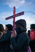 A Protester holds a pink cross with the name of Isabel Cabanillas on the Paso del Norte International Bridge in Ciudad Juarez, Mexico on January 25, 2020. The 26-year-old was an artist and activist  murdrered in the early hours of January in downtown Juarez, whose violent death has sparked outrage among the community.  She is the eighth woman to be murdered in the city this year.