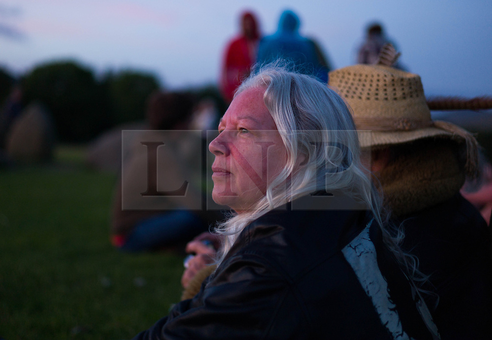 © Licensed to London News Pictures. <br /> 20/06/2014. <br /> <br /> Castlerigg Stone circle, Cumbria, England<br /> <br /> Visitors to the ancient site of Castlerigg Stone Circle near Keswick in Cumbria sit and watch the sunset on the evening of the Summer Solstice.<br /> <br /> Photo credit : Ian Forsyth/LNP