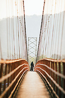 Neriamangalam, India -- February 17, 2018: A nun walks across a suspension bridge on the Periyar River in Kerala.