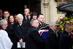 © Licensed to London News Pictures. 01/02/2017. Watford, UK. RITA TAYLOR (left), wife of Graham Taylor is joined by other family members as they watch the coffin leave the church, during the funeral of former England football team manager Graham Taylor at St Mary's Church in Watford, Hertfordshire. The former England, Watford and Aston Villa manager,  who later went on to be chairman of Watford Football Club, died at the age of 72 from a suspected heart attack. Photo credit: Ben Cawthra/LNP