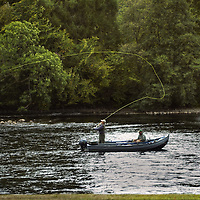Fishermen casting from a boat in the  River Tay, Dunkeld, Scotland<br />