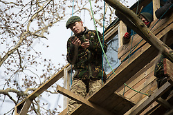 Steeple Claydon, UK. 23 February, 2021. Anti-HS2 activist Lazer Sandford observes National Eviction Team bailiffs from a tree house during an operation by HS2 Ltd to evict activists living in ancient woodland known as Poors Piece. The activists created the Poors Piece Conservation Project there in spring 2020 after having been invited to stay on the land by its owner, farmer Clive Higgins. Already, local village communities have been hugely impacted by HS2, with 550 acres of land seized including a large section of a nature reserve.