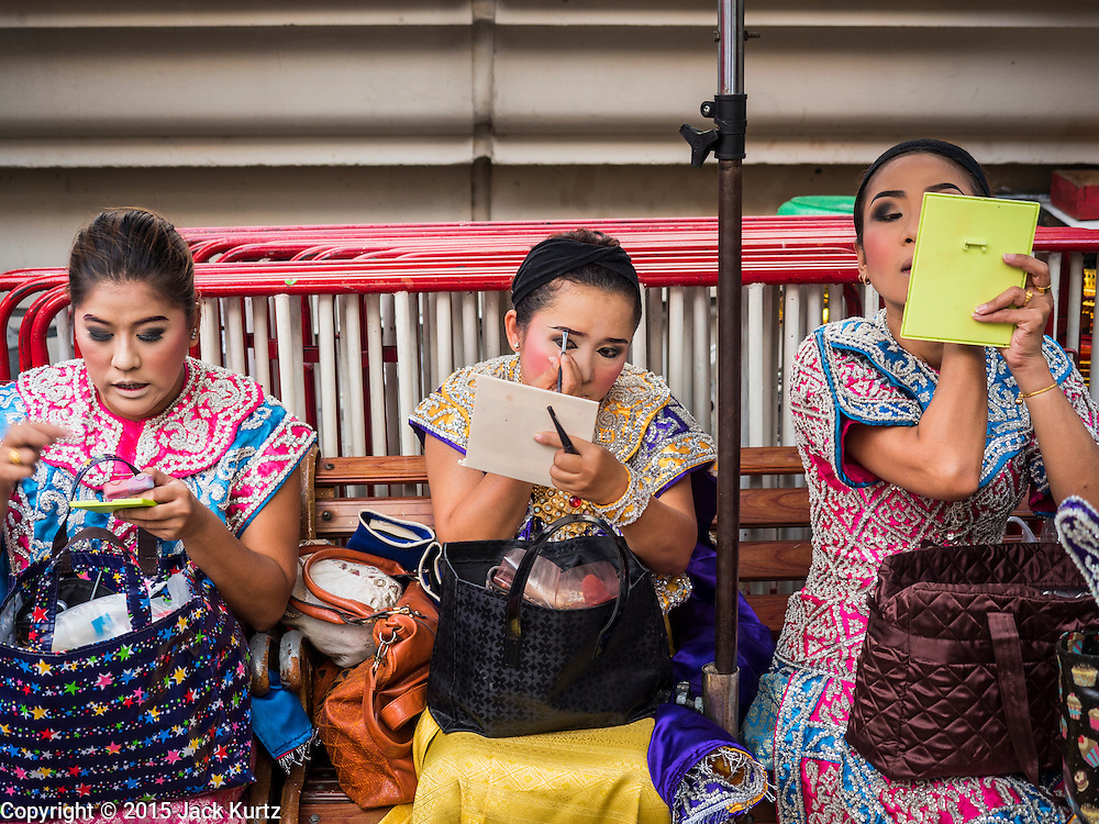"""04 SEPTEMBER 2015 - BANGKOK, THAILAND:  Dancers get ready to perform for a special ceremony at the Erawan Shrine. A """"Holy Religious Ceremony for Wellness and Prosperity of our Nation and Thai People"""" was held Friday morning at Erawan Shrine. The ceremony was to regain confidence of the Thai people and foreign visitors, to preserve Thai religious customs and traditions and to promote peace and happiness inThailand. Repairs to Erawan Shrine were completed Thursday, Sept 3 after the shrine was bombed on August 17. Twenty people were killed in the bombing and more than 100 injured. The statue of the Four Faced Brahma in the shrine was damaged by shrapnel and a building at the shrine was damaged by debris.    PHOTO BY JACK KURTZ"""
