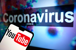A Youtube logo seen displayed on a mobile phone with an illustrative model of the Coronavirus displayed on a monitor in the background. Photo credit should read: James Warwick/EMPICS Entertainment